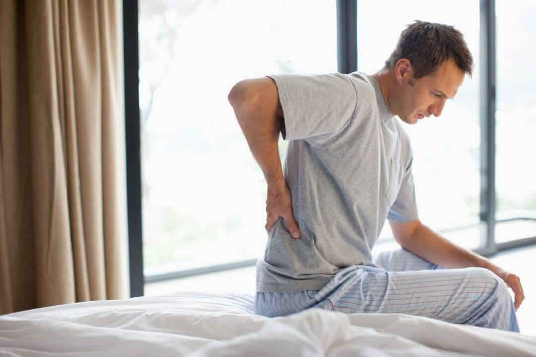 man-sitting-on-bed-with-backache-170510558-5890f6075f9b5874ee9480a7