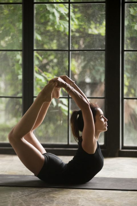 young-attractive-woman-dhanurasana-pose-studio-background_1163-4553